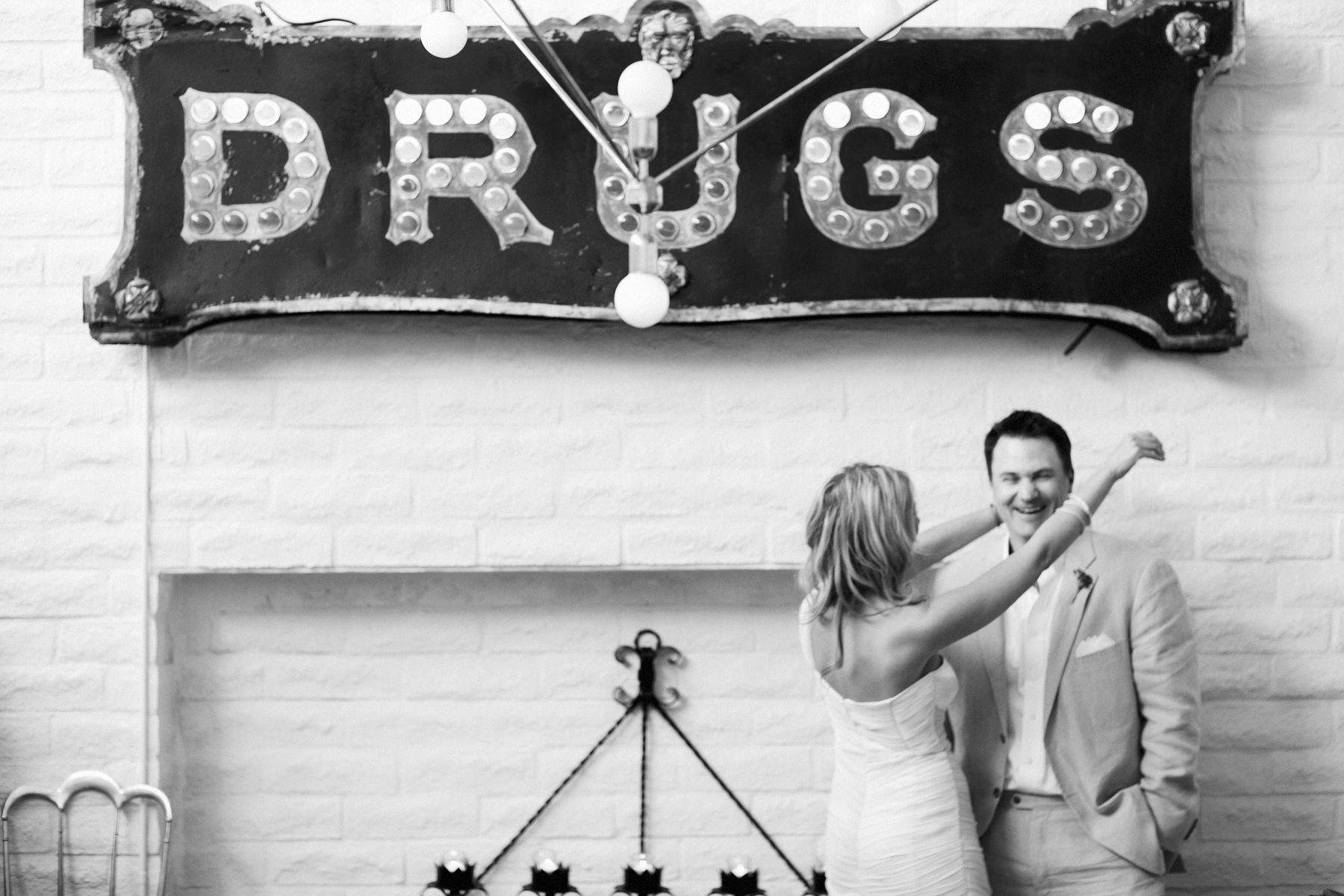 parker palm springs wedding photographer nicole caldwell couple in front of drugs sign in lobby